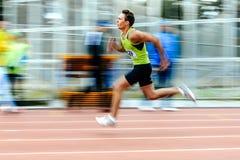 blurred motion sprinter runner running man race in 200 meters Royalty Free Stock Image