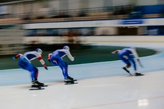 Blurred motion three women athletes speed skaters. In warm up royalty free stock image