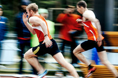 Blurred motion two runners men run in stadium Royalty Free Stock Photos