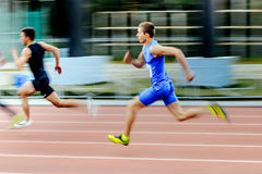Blurred motion two sprinters runners men run race in 200 meters Royalty Free Stock Photo