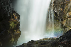 Blurred motion of a waterfall with a rainbow in mist. Stock Photo
