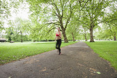 Blurred motion of woman jogging in park Royalty Free Stock Images