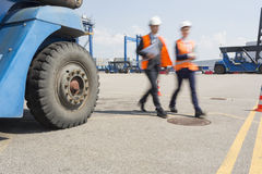 Blurred motion of workers walking in shipping yard Royalty Free Stock Photos