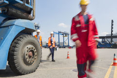 Blurred motion of workers walking in shipping yard Stock Photos