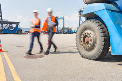 Blurred motion of workers walking in shipping yard Royalty Free Stock Photo