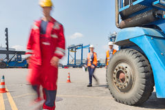 Blurred motion of workers walking in shipping yard Royalty Free Stock Images