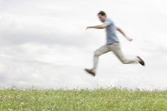 Blurred motion of young man jumping in park against sky Royalty Free Stock Image