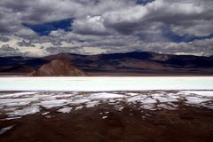Blurred mountain range under dramatic cloud carpet contrasting with white and blue shimmering salt lake royalty free stock photos