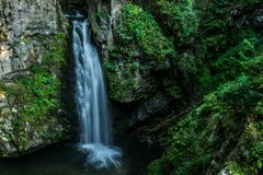 Blurred mountain waterfall in the forest. royalty free stock image