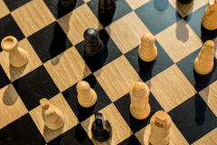 Blurred natural wood grain chess board showing battle of pawns a Stock Photo
