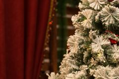 Blurred New Year background. Festive Christmas tree near the red curtains. Stock Image