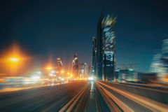Blurred night city background with illuminated architecture of Dubai, UAE. Royalty Free Stock Images