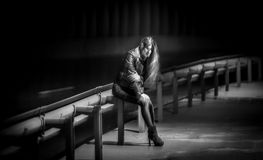 Blurred night shot of lonely woman sitting on railings at highwa Stock Photo