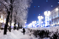 Blurred night snowy street background with winter holiday lights royalty free stock photography