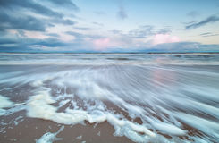 Blurred North sea wave at sunrise Stock Photos