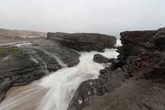 Blurred ocean waves flowing down on shore rocks Stock Photos