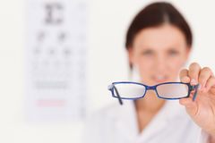 Blurred optician showing glasses Stock Photography