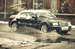 Blurred out. Black car rides on big puddle in snowy day. Stock Photography