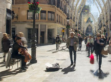 Blurred pedestrains and Busker in Southern Spain. A street musician plays the cello in Calle Larios Malaga as blurred pedestrains walk past Stock Photo