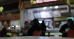 Blurred People in front of counter of fast food in food court of mall stock video
