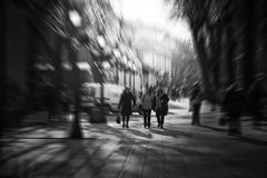 Blurred people walking on city street. Black and white photo Stock Image