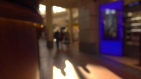 Blurred people walking in modern shopping center against sun. 4K background bokeh video stock footage