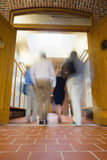 Blurred people walking through open doors Stock Photo