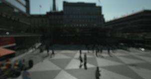 Blurred people walking in Plattan square in central Stockholm on a sunny day. stock footage