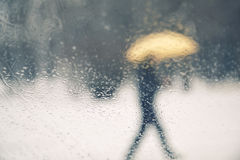 Blurred person with umbrella walking background Stock Image