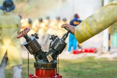 Blurred photo firemen using water from hose for fire fighting at fire fight training of insurance group.Firefighter wearing a fire royalty free stock images