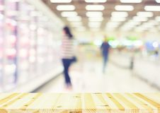Supermarket blurred background. Blurred photo of fresh food in supermarket or shopping mall montage with wood table for background stock photos