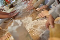 People at cooking classes. Blurred photo of people cooking cake at cooking classes stock images