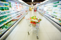 Blurred photo of shopping trolley. Blurred shopping trolley full of water bottles, fruits and vegetables standing between two refrigerators with dairy products Stock Photos