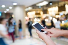 Blurred photo and smartphone on shopping mall and people with bo. Keh Stock Photography