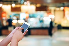 Blurred photo and smartphone on shopping mall and people with bo. Keh Stock Photos