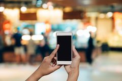 Blurred photo and smartphone on shopping mall and people with bo. Keh Stock Image