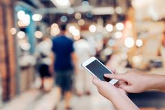 Blurred photo and smartphone on shopping mall and people with bo. Keh Stock Photo