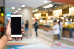 Blurred photo and smartphone on shopping mall and people with bo. Keh Royalty Free Stock Photography