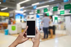 Blurred photo and smartphone on shopping mall and people with bo. Keh Royalty Free Stock Photos