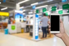 Blurred photo and smartphone on shopping mall and people with bo. Keh Stock Images