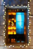 Sparkle garland on window. Blurred photo of window decorated with bright electric garland Stock Photos