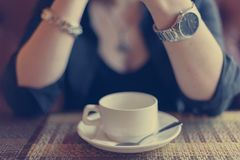 Blurred photo of woman sitting in cafe at a cup of coffee on the woman`s hands watches and a bracelet. Blurred photo of woman sitting in cafe at a cup of coffee stock photo