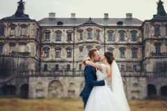 A blurred picture of a bride and groom kissing in the front of a. N old castle Royalty Free Stock Photos