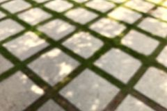 Blurred Picture of Concrete Block Floor in the garden ground, Blurred of Brick with manicured lawn background. The Blurred Picture of Concrete Block Floor in the royalty free stock photos