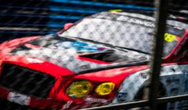 Blurred picture of fence mesh netting and car on racetrack background. Motorsport car racing on asphalt road. Super racing car. On street circuit. Automotive stock photography