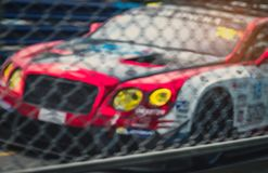 Blurred picture of fence mesh netting and car on racetrack background. Motorsport car racing on asphalt road. Super racing car. On street circuit. Automotive royalty free stock photo