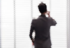 Blurred picture of young business man negotiate about his task. Near the window in office building stock photo