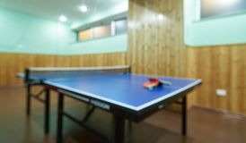 Blurred Ping pong table, rackets and balls in a sport hall. Tabletennis game, close-up Royalty Free Stock Image