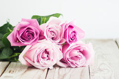 Blurred pink roses on wooden background. Blurred pastel roses on grey wooden background Stock Photo