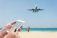 Blurred plane and blue sea with white sand beach. Women using smartphone top on blurred blue sea with some people relax on the white sand beach - Can used for Stock Photography